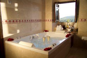 baño de suite con copas y petalos